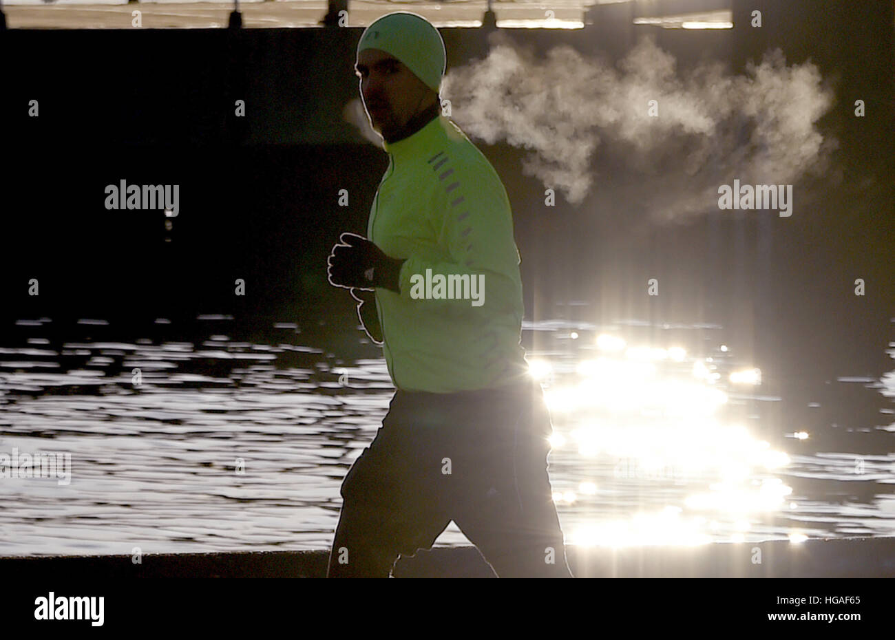 Kiel, Germany. 06th Jan, 2017. A jogger runs along the Foerde river shortly after sunrise in Kiel, Germany, 06 January Stock Foto