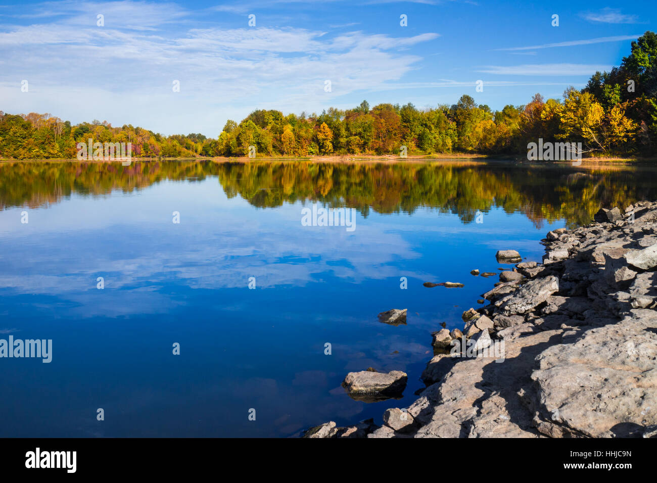 Early fall colors are reflected in the still blue waters of Bluecat Lake in southern Tennessee Stock Photo