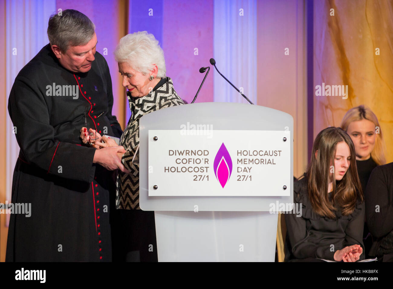 Cardiff, Wales, Uk. 27th Jan, 2017.  Holocaust survivor Eva Clarke is supported by The Reverend Canon Stewart Lisk Stock Foto