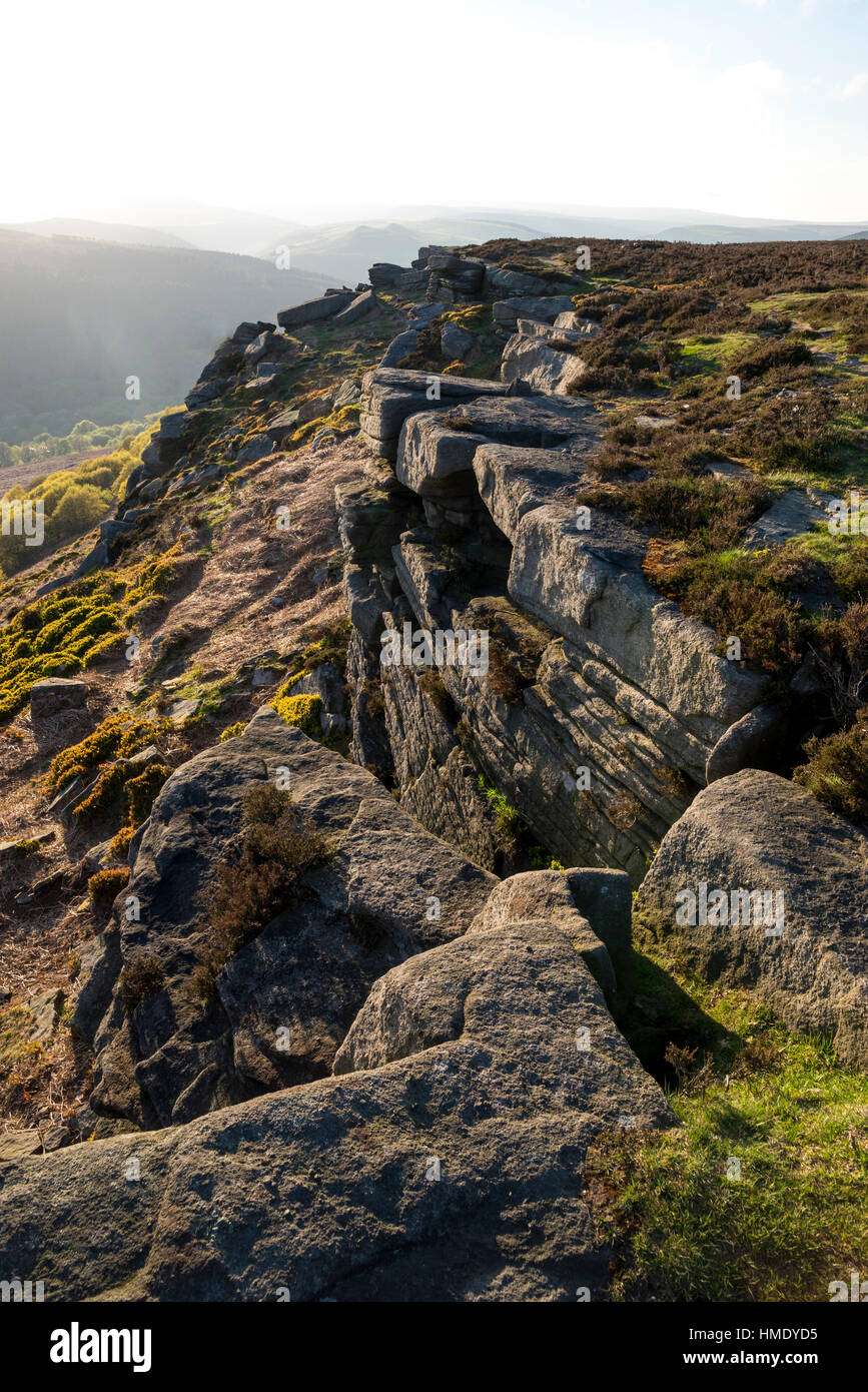 Rocks on Bamford edge in the Peak District park with summer sunlight on the hillside. A rugged Derbyshire landscape. Stock Photo