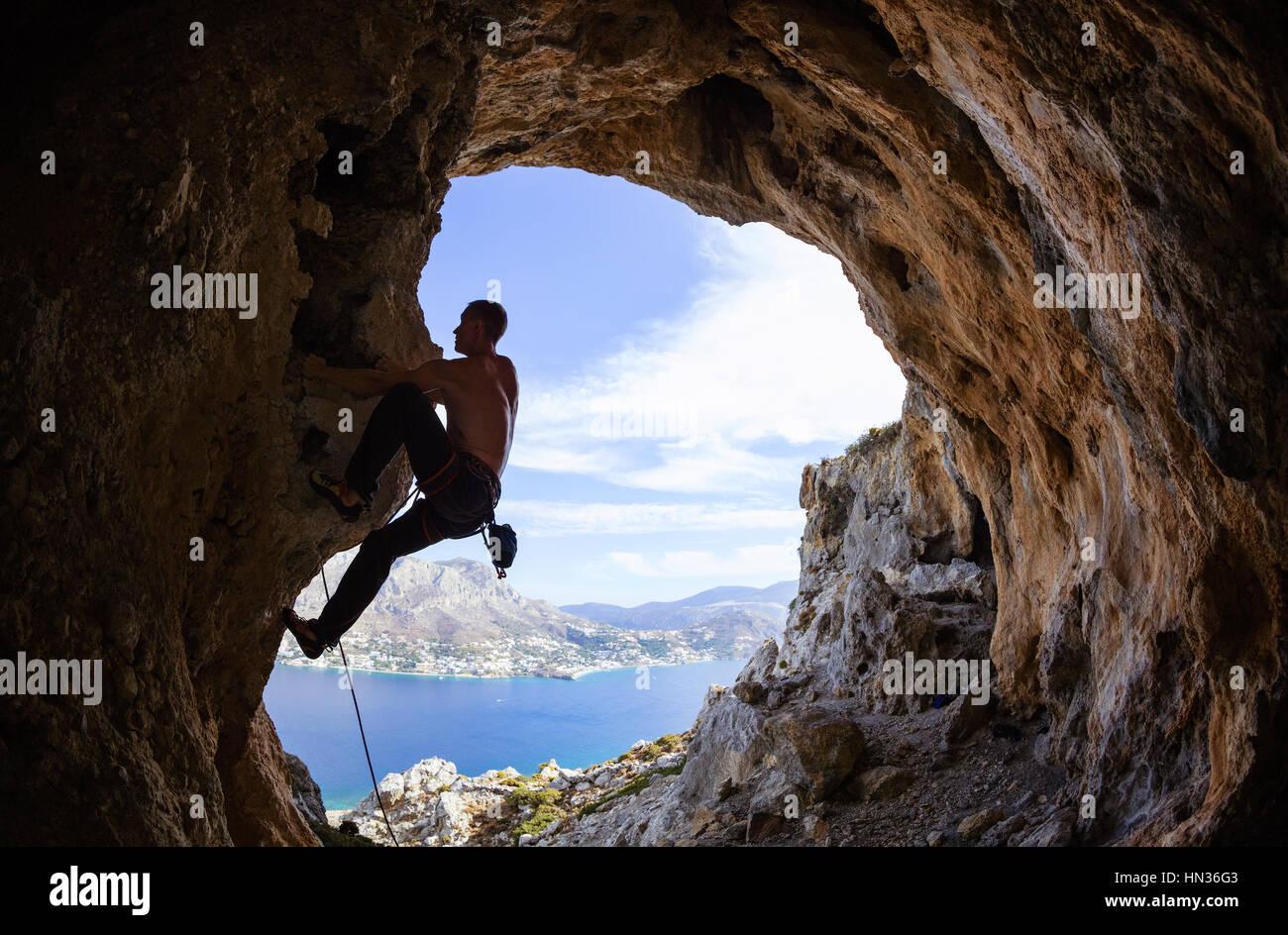 Young man climbing along rocks Stock Foto