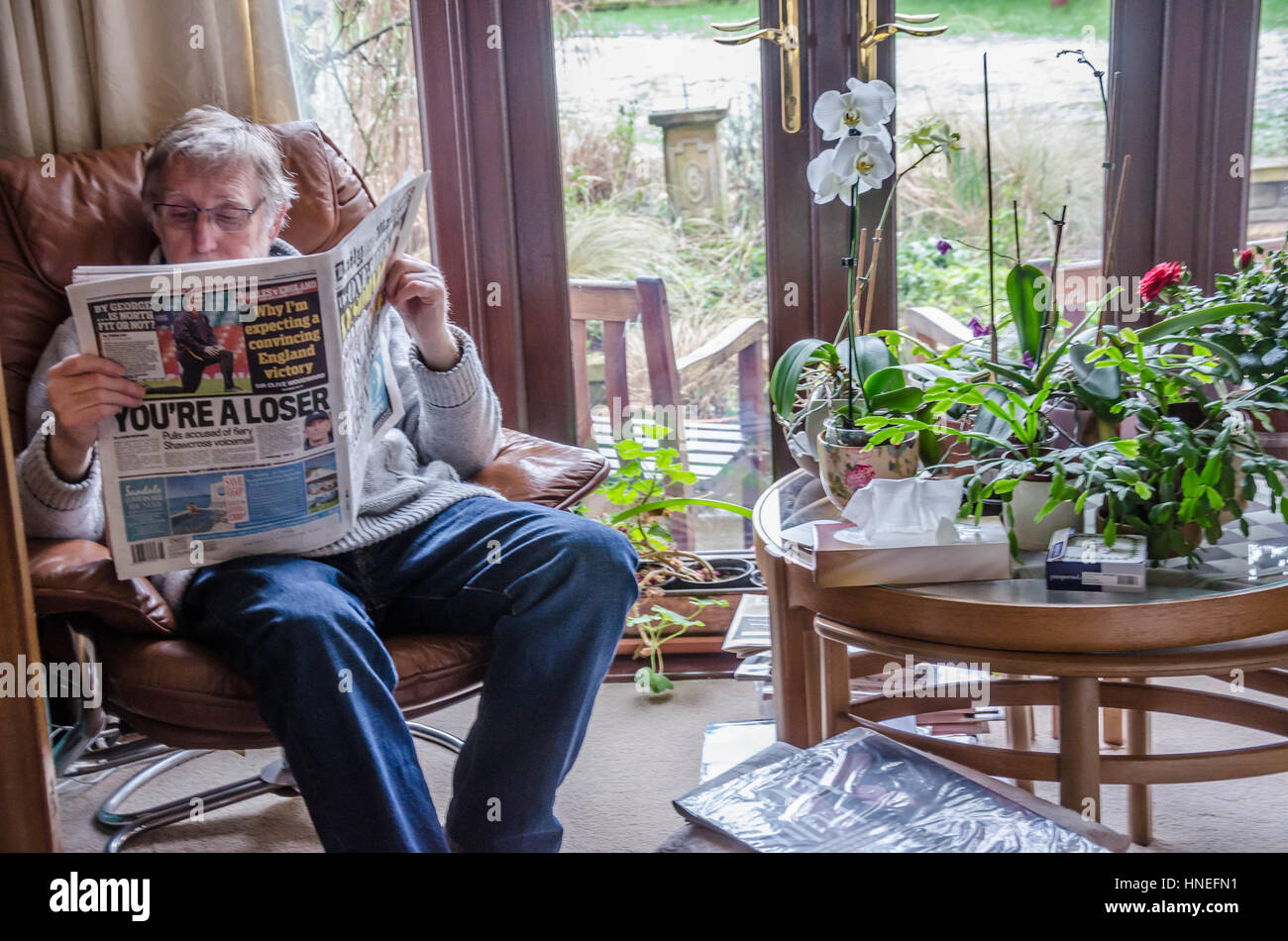 a-man-sits-in-a-comfy-armchair-reading-the-daily-mail-newspaper-HNEFN1.jpg
