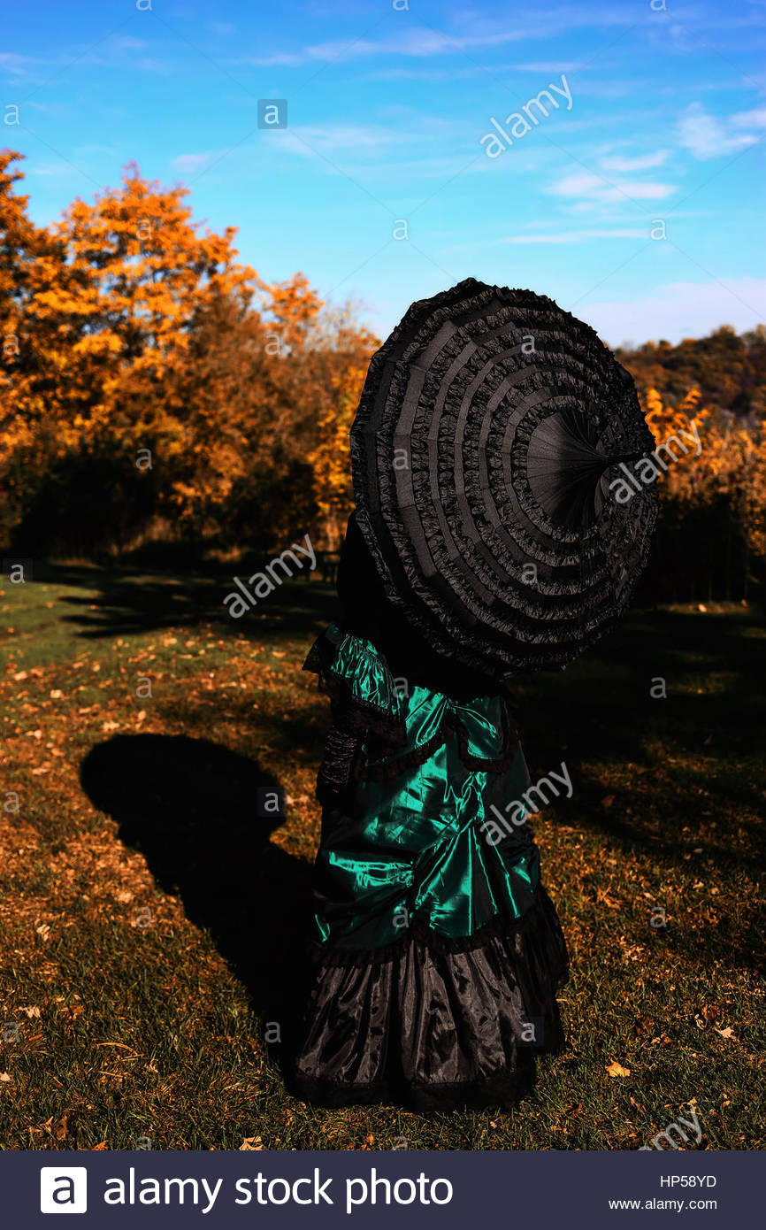 Rear view of Victorian woman holding an umbrella Stock Foto
