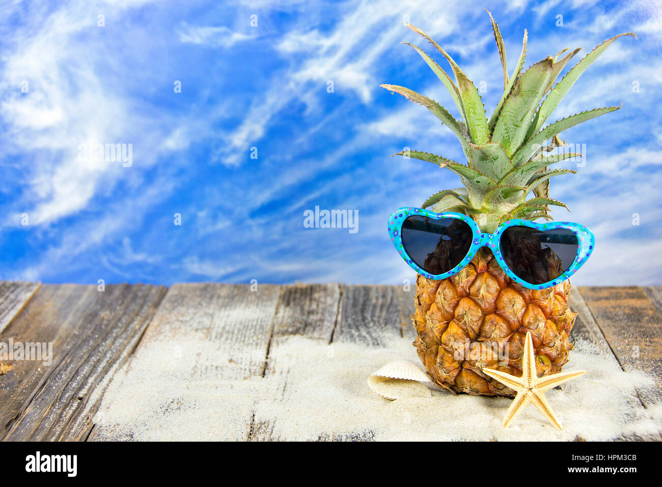 pineapple wearing sunglasses in sand with seashell and ...