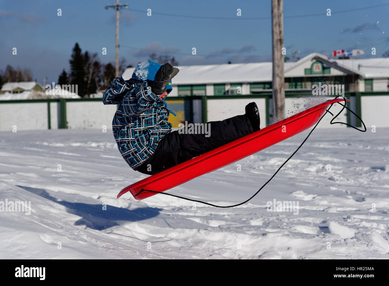 a-young-boy-4-yrs-old-jumping-into-the-air-on-a-sledge-in-quebec-winter-HR25MA.jpg