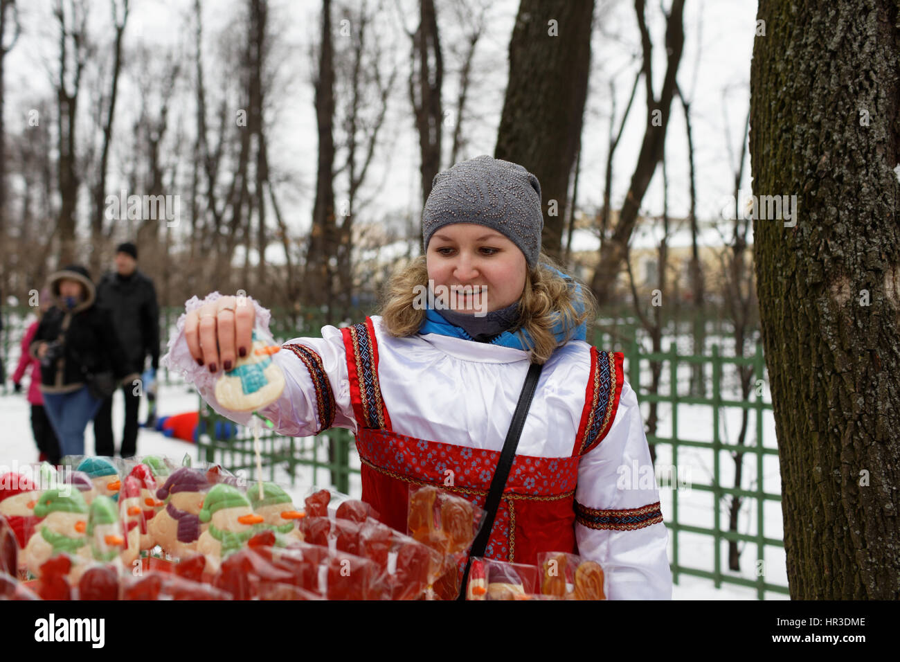 St. Petersburg, Russia, 26th February, 2017. Woman selling sweets on stick during Shrovetide celebrations in the Stock Photo