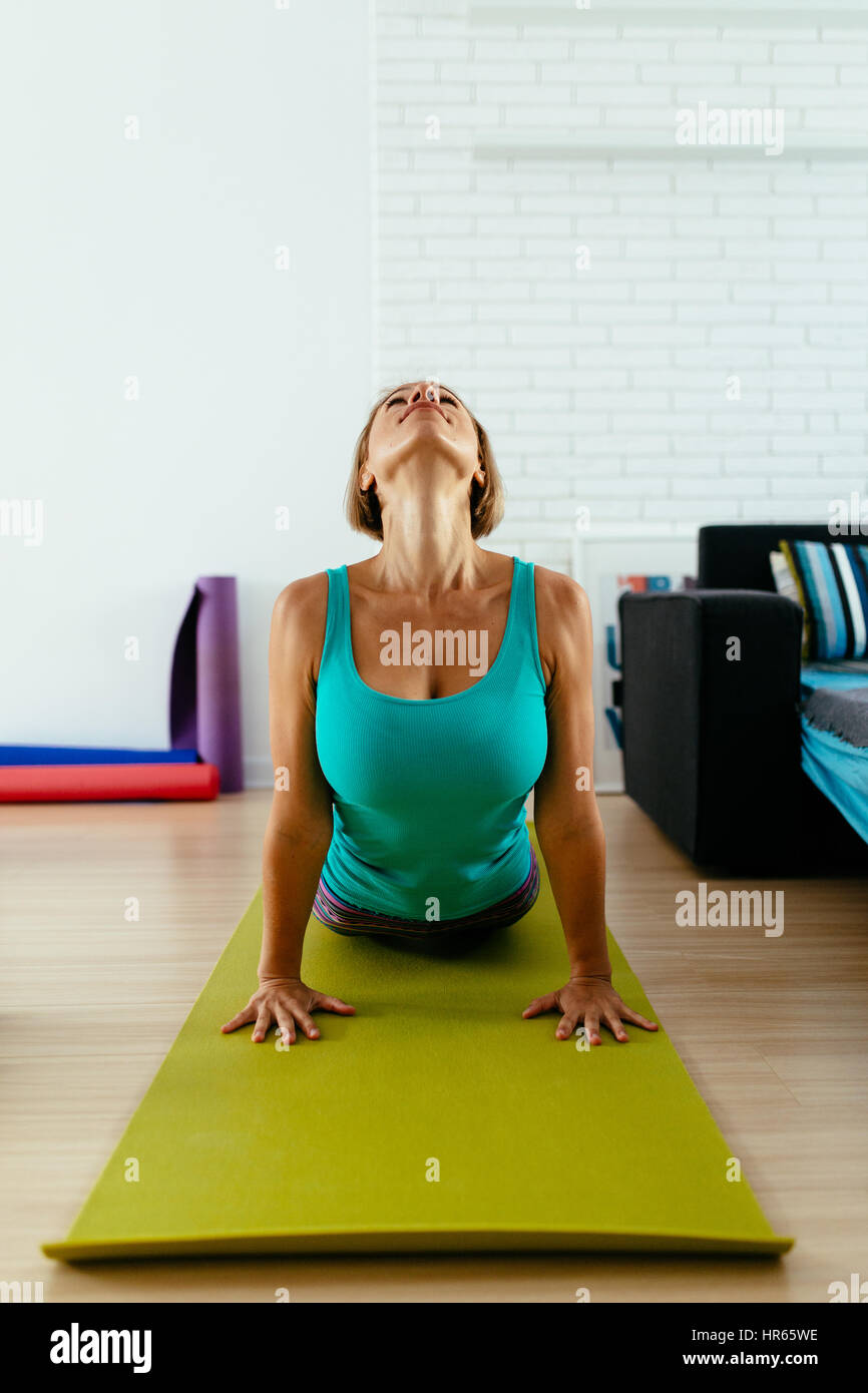 athletic woman practicing yoga on a green mat indoor. vertical photo Stock Foto