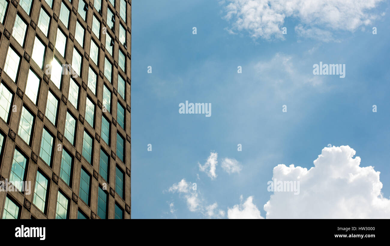 The bright sun of a sunny summer day reflecting off of the glass of a buildings exterior with white cloud in the Stock Photo