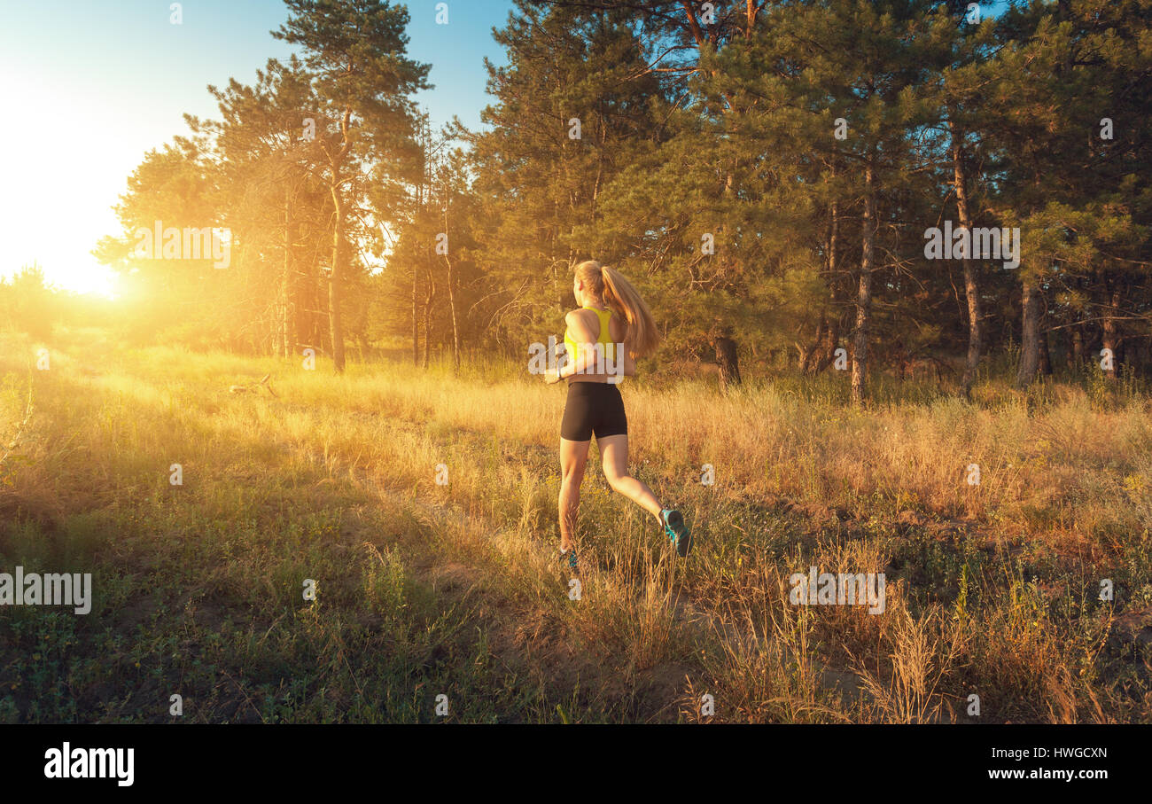 Young sporty girl running on a field near the trees at sunset in summer. Athlete running on the off road in the Stock Foto