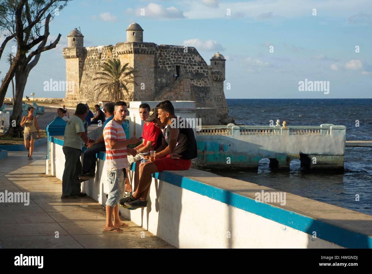 Cuba, Cojimar, young people seated in the seaside promenade in front of a colonial fort, in this village once frequented Stock Photo