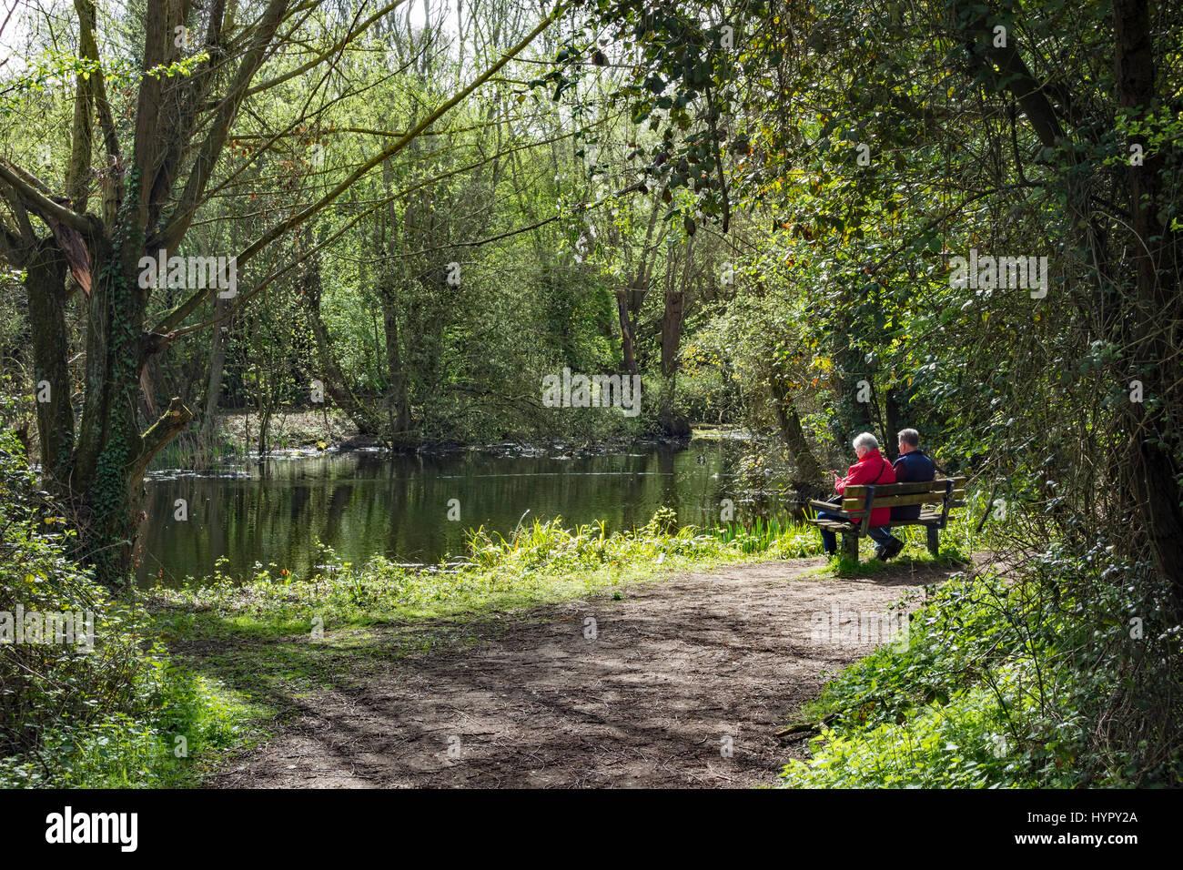 older-couple-sitting-on-bench-beside-lak