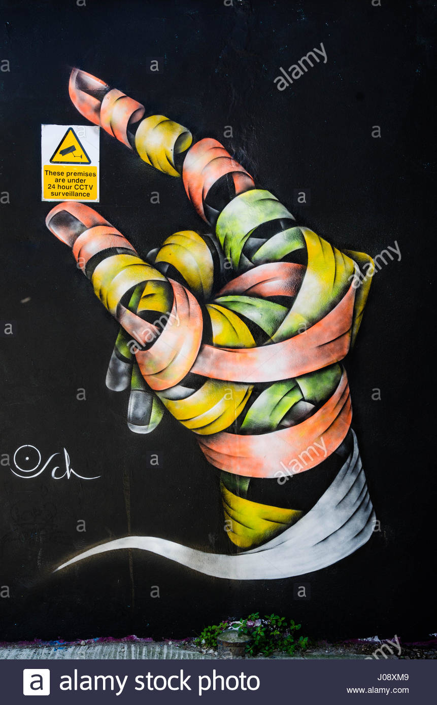 mural-on-a-black-background-of-a-hand-made-up-of-colourful-bandages-J08XM9.jpg