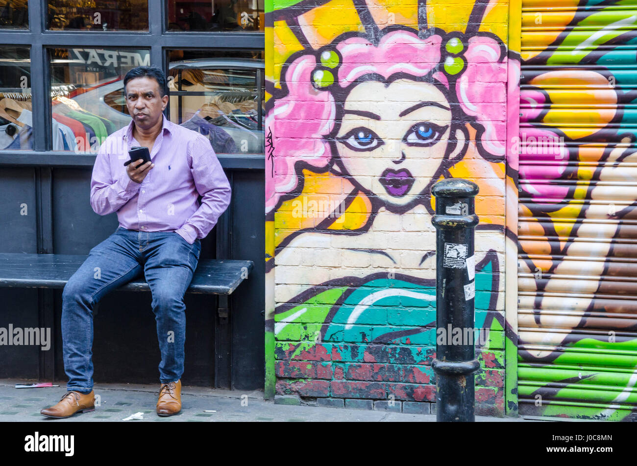 a-man-sits-on-a-bench-next-to-a-shop-on-hanbury-street-in-east-london-J0C8MN.jpg