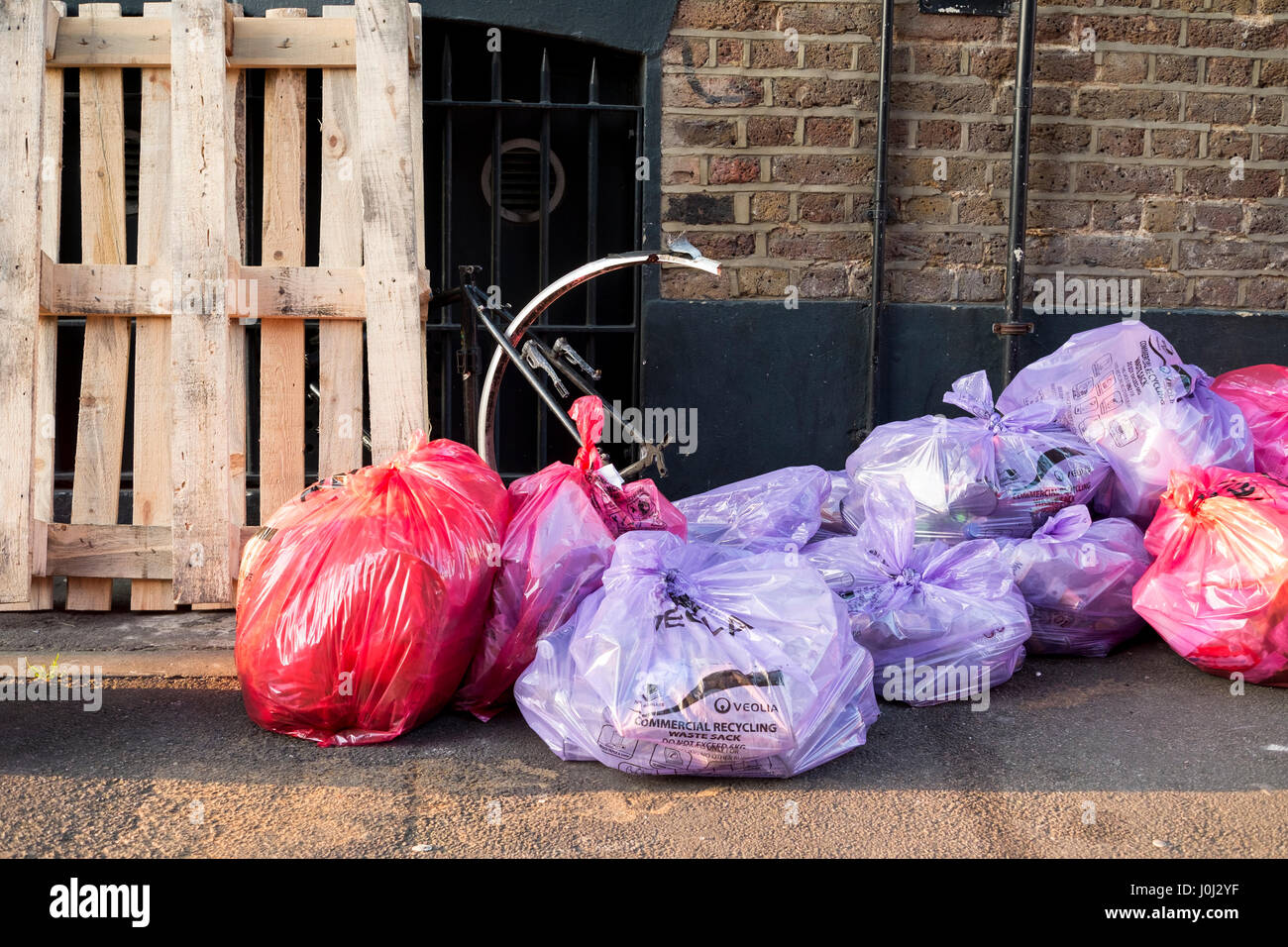 Bags of commercial rubbish and recycling left out for collection Stock Photo