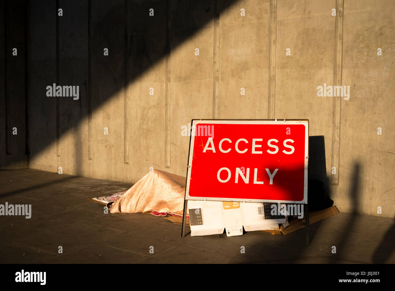 A homeless person sleeps between an Access Only road sign and a solid concrete wall - Liverpool Street, London April Stock Photo