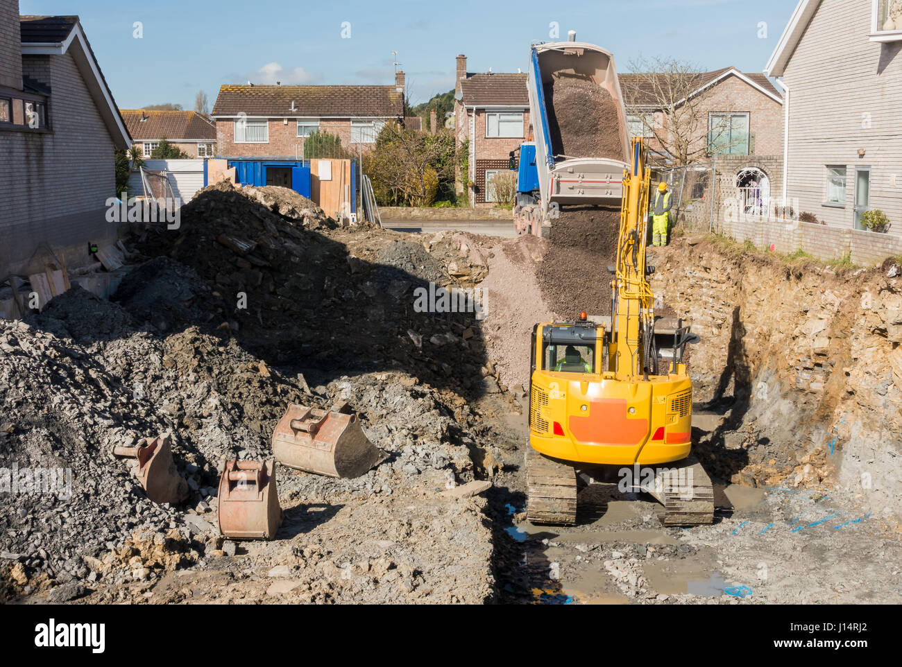 Excavator is digging a house foundation in a residential for Digging foundation for house
