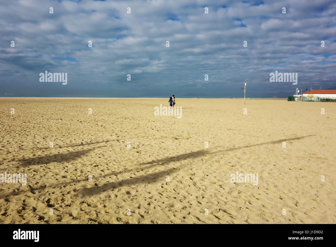 lone-woman-walking-on-a-sand-beach-in-wi