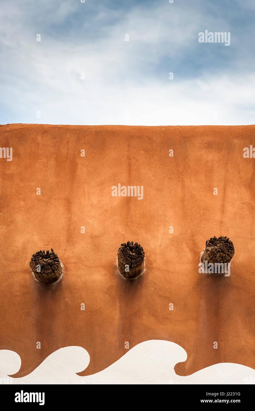 barred-adobe-wall-with-three-visible-woo