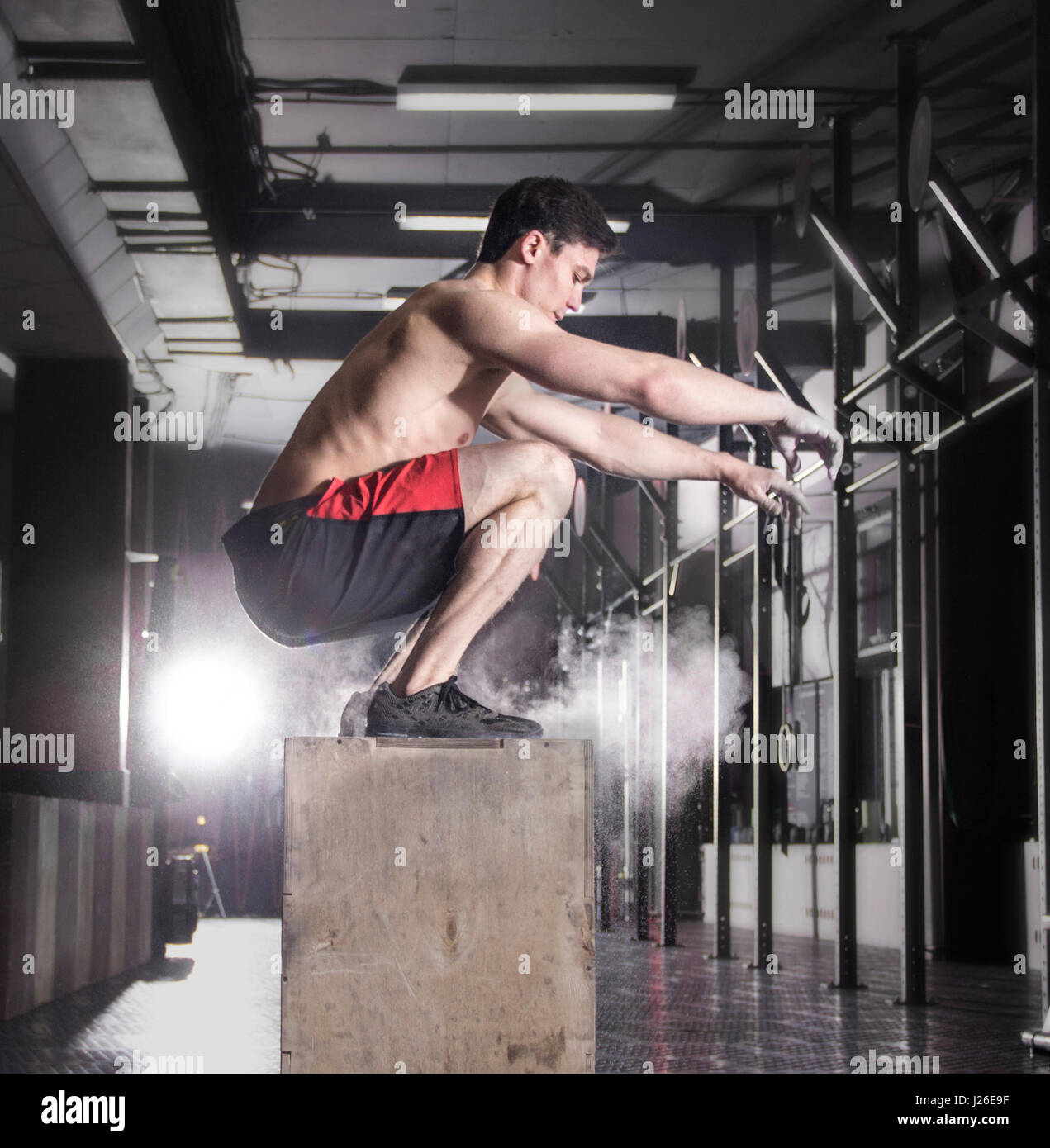 Fit young man box jumping at a crossfit gym.Athlete is performin Stock Foto