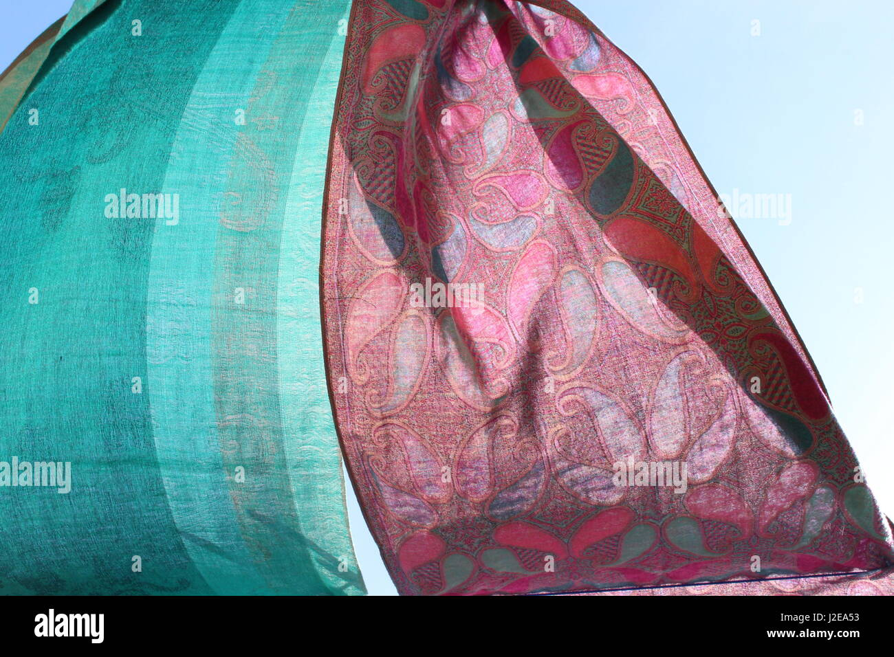 2 silk scarves, pink and turquoise, blowing in the breeze against a summer blue sky Stock Photo