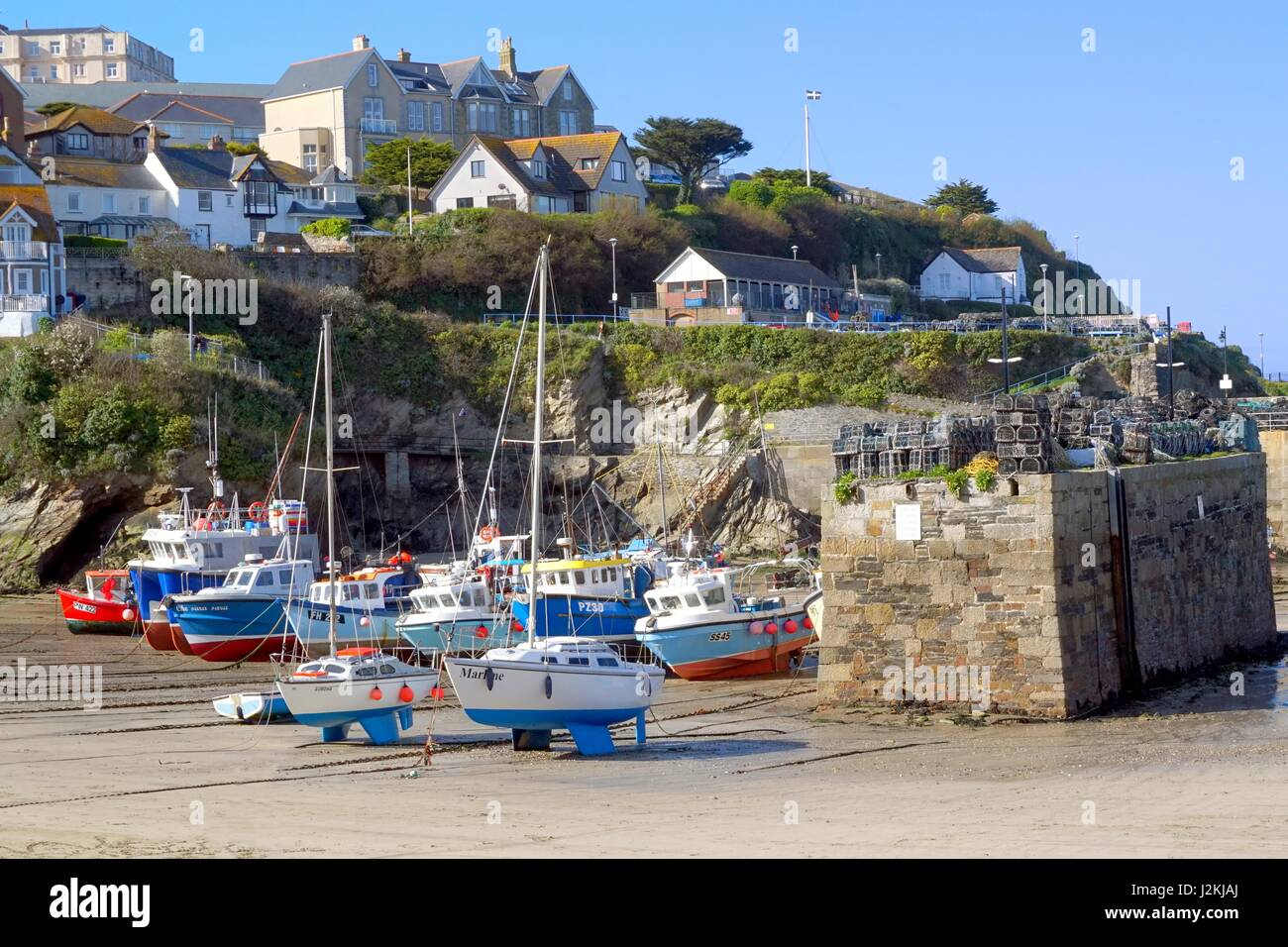 Newquay, Cornwall, UK - April 1 2017: Colourful fishing and sailing boats on the sand in Newquay harbour at low Stock Photo