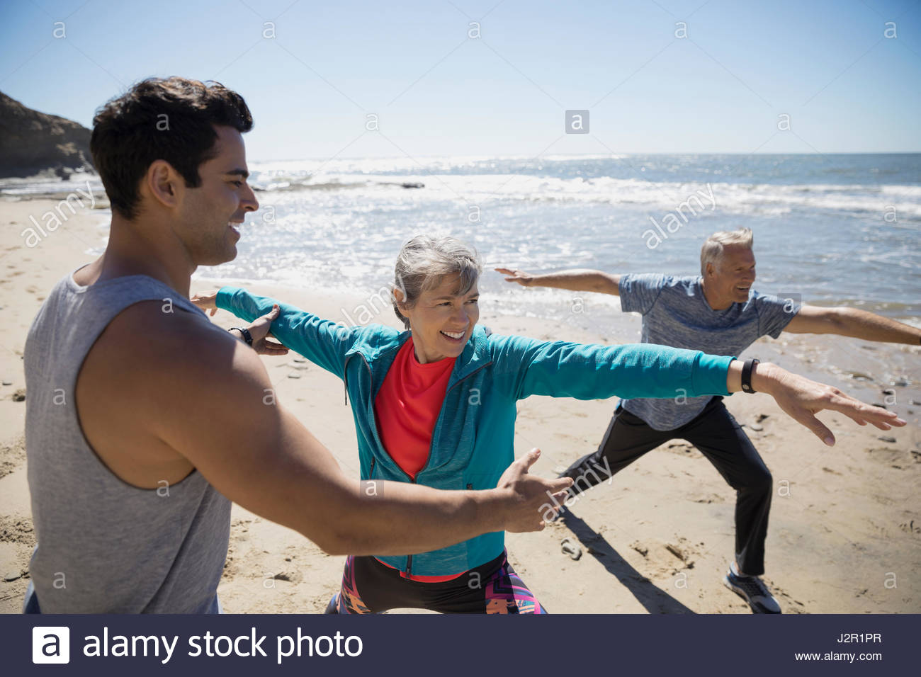 Crossfit trainer helping senior couple exercising, practicing yoga warrior 2 pose on sunny beach Stock Foto