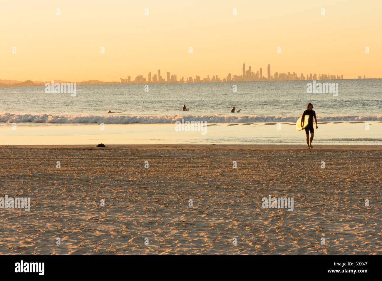 surfer-walks-away-from-the-sea-on-coolan