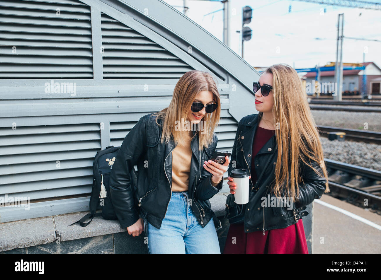 Two Women Talking in the City.Outdoor lifestyle portrait of two best friends hipster girls wearing stylish Leather Stock Photo