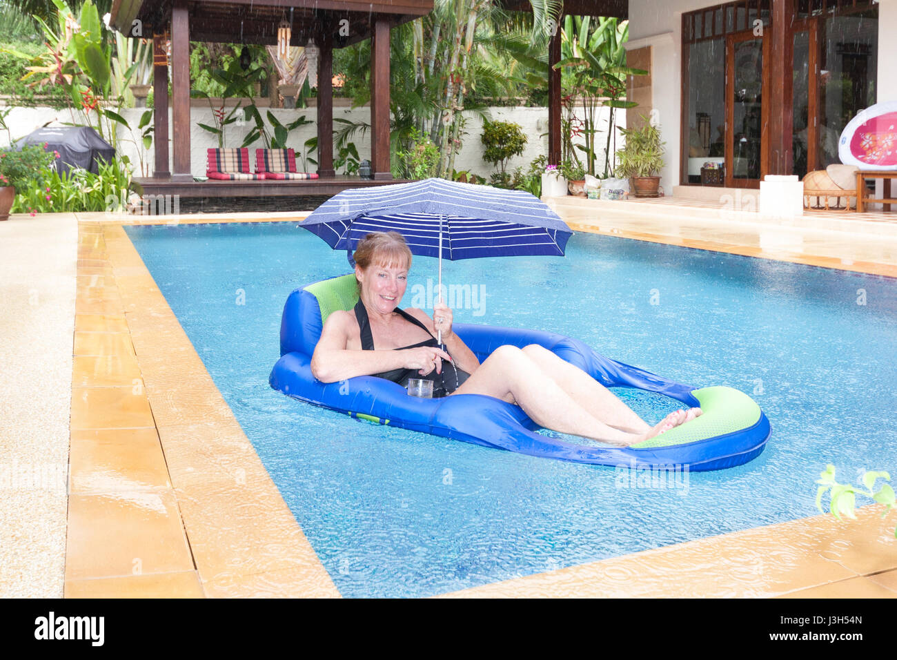 senior-woman-on-louger-in-swimming-ool-i