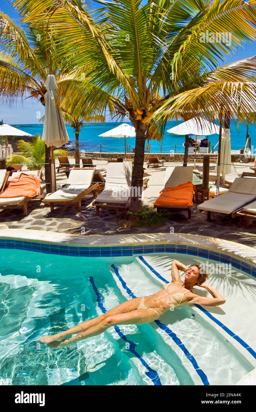 Young woman sunbathing in swimming pool wicked weasel for Swimming pool mauritius