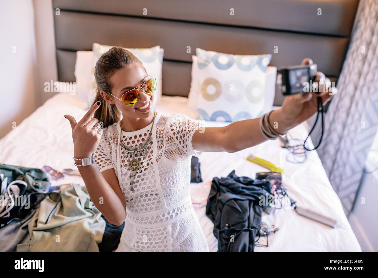 Female vlogger recording broadcast with digital camera. Woman taking a selfie video displaying fashion clothing - Stock Image
