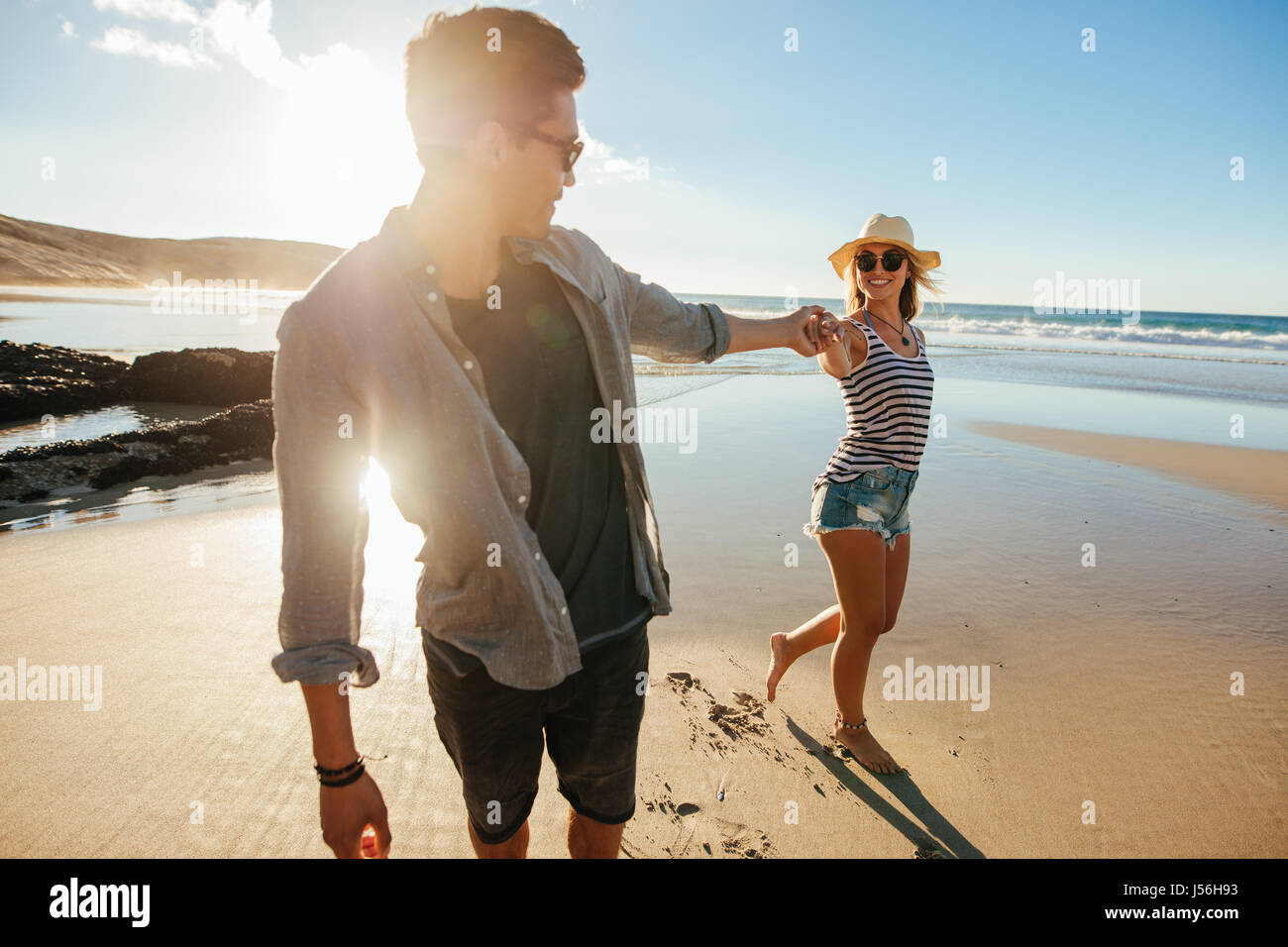 Shot of loving young couple holding hands and walking on seashore. Young man and woman walking on beach on a summer - Stock Image