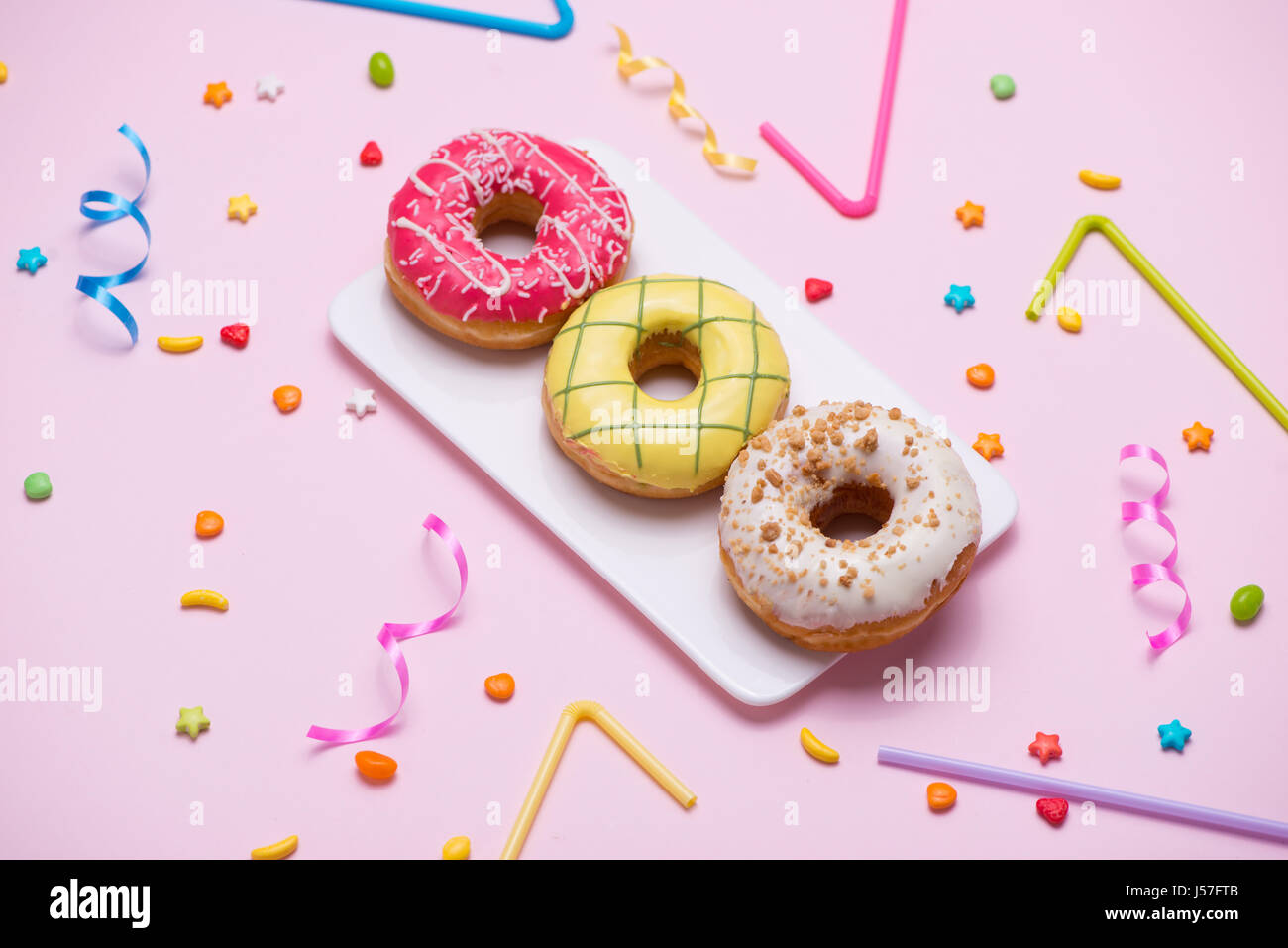 Party. Different colourful sugary round glazed donuts and bottles of drinks on pink background. - Stock Image
