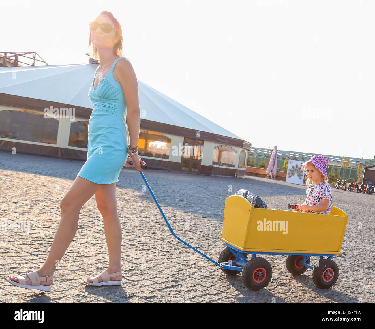a-mother-carries-a-daughter-in-a-cart-co