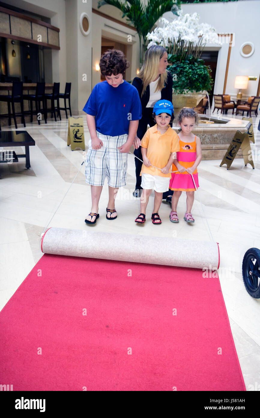 Orlando Florida International Drive The Peabody Orlando hotel lobby Duck March woman girl boy children help tradition - Stock Image