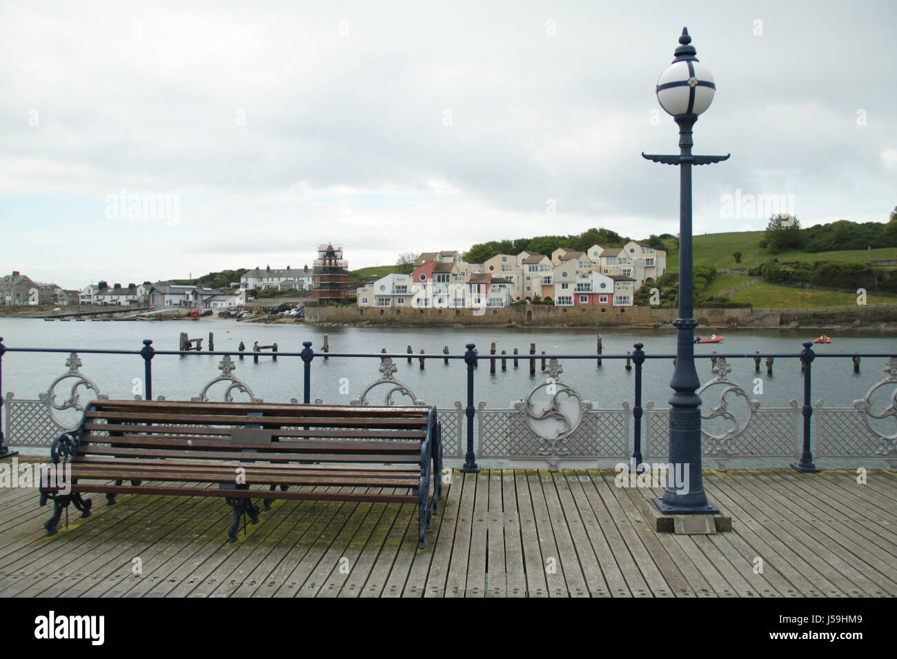 Swanage, UK -  12 May: A public bench on the Swanage pier. General view of the seaside town of Swanage in Dorset, - Stock Image