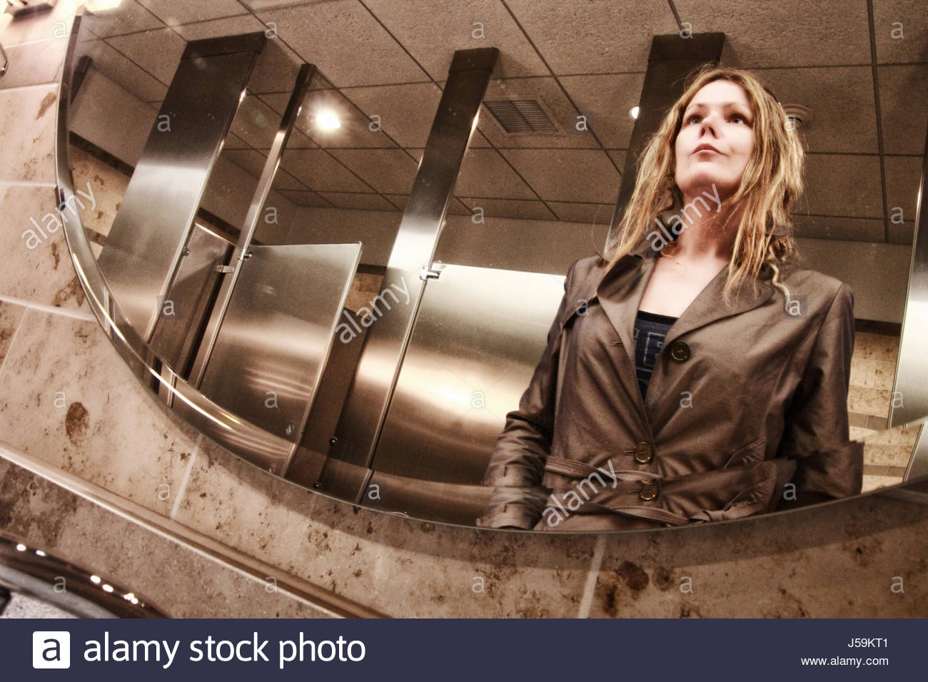 Woman looking at her reflection in the mirror in public washroom - Stock Image