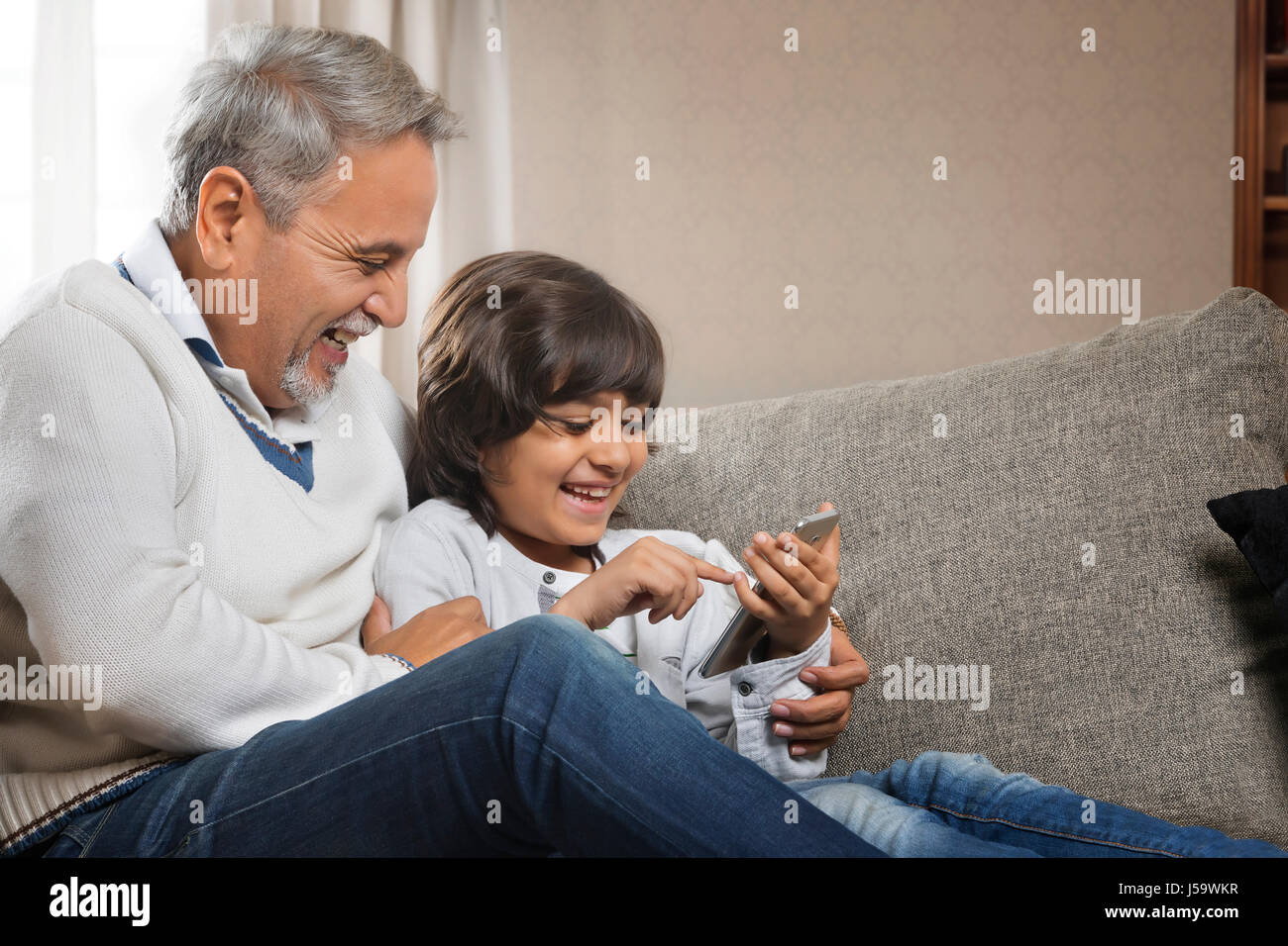 Happy grandfather and grandson using cell phone - Stock-Bilder