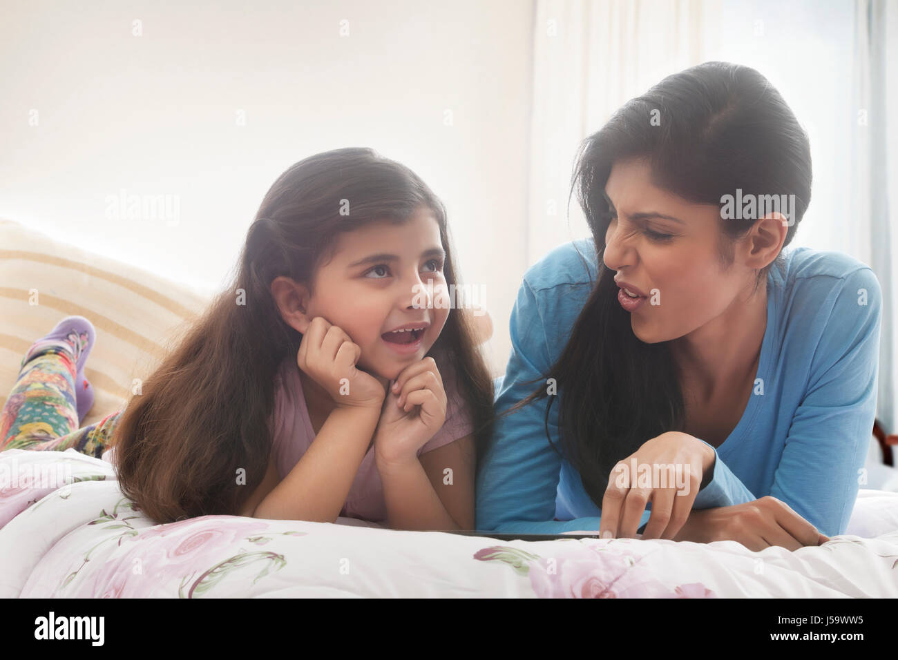 Mother and daughter lying in bed and talking - Stock-Bilder