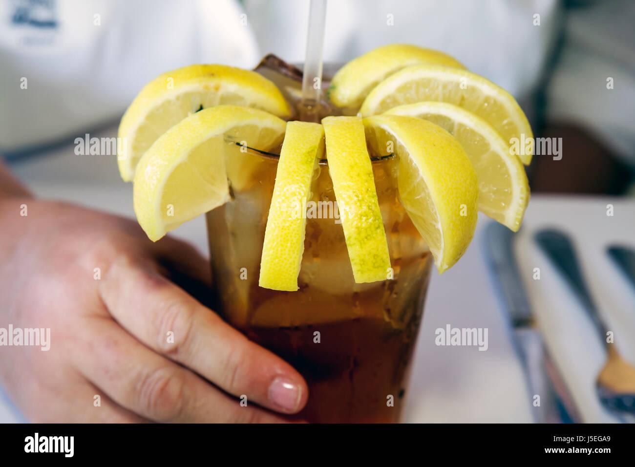 Savannah Georgia Historic District River Street Huey's New Orleans Style Restaurant iced tea cup many lemon - Stock Image