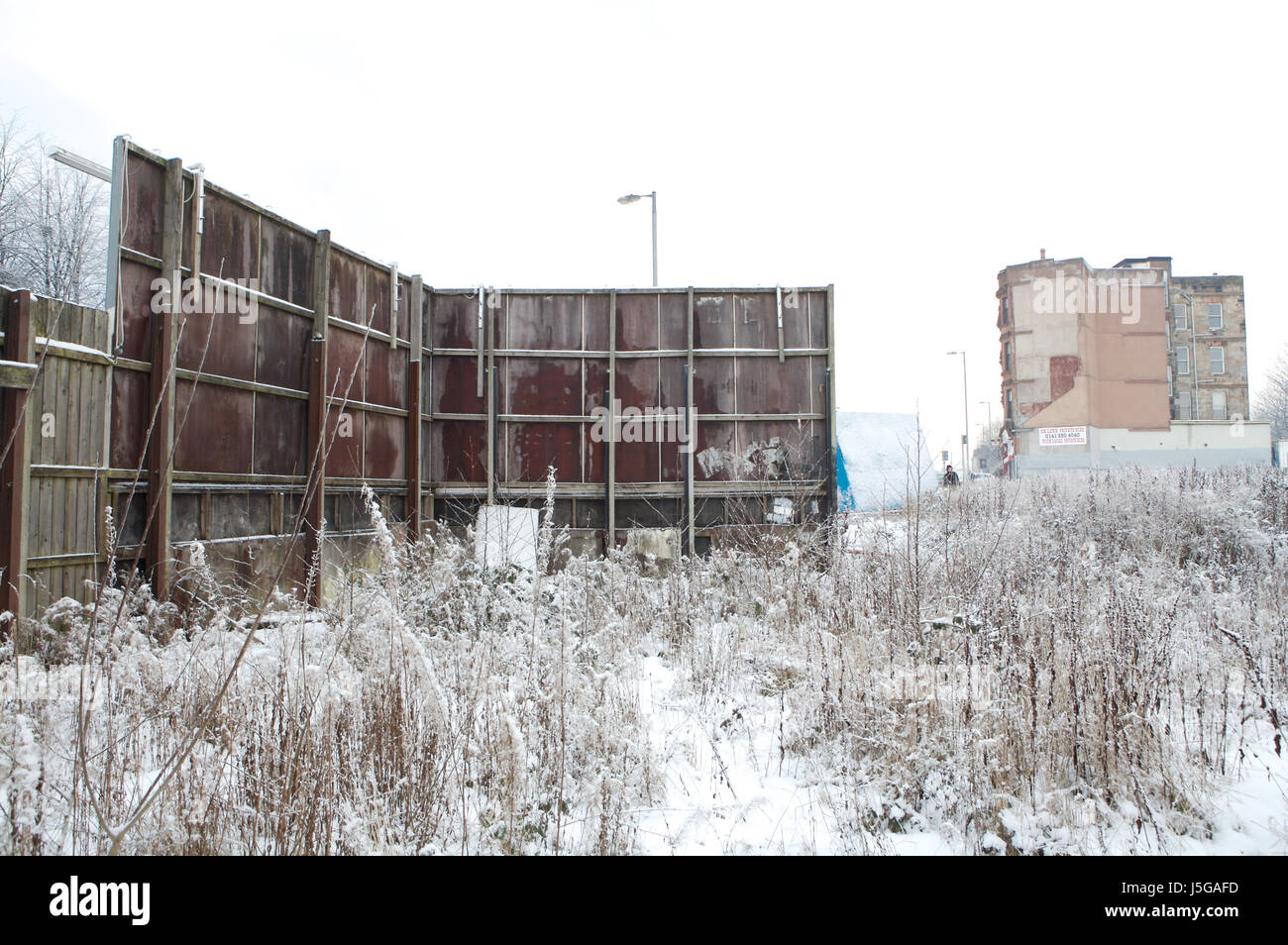 View from behind billboards in East End of Glasgow. - Stock Image
