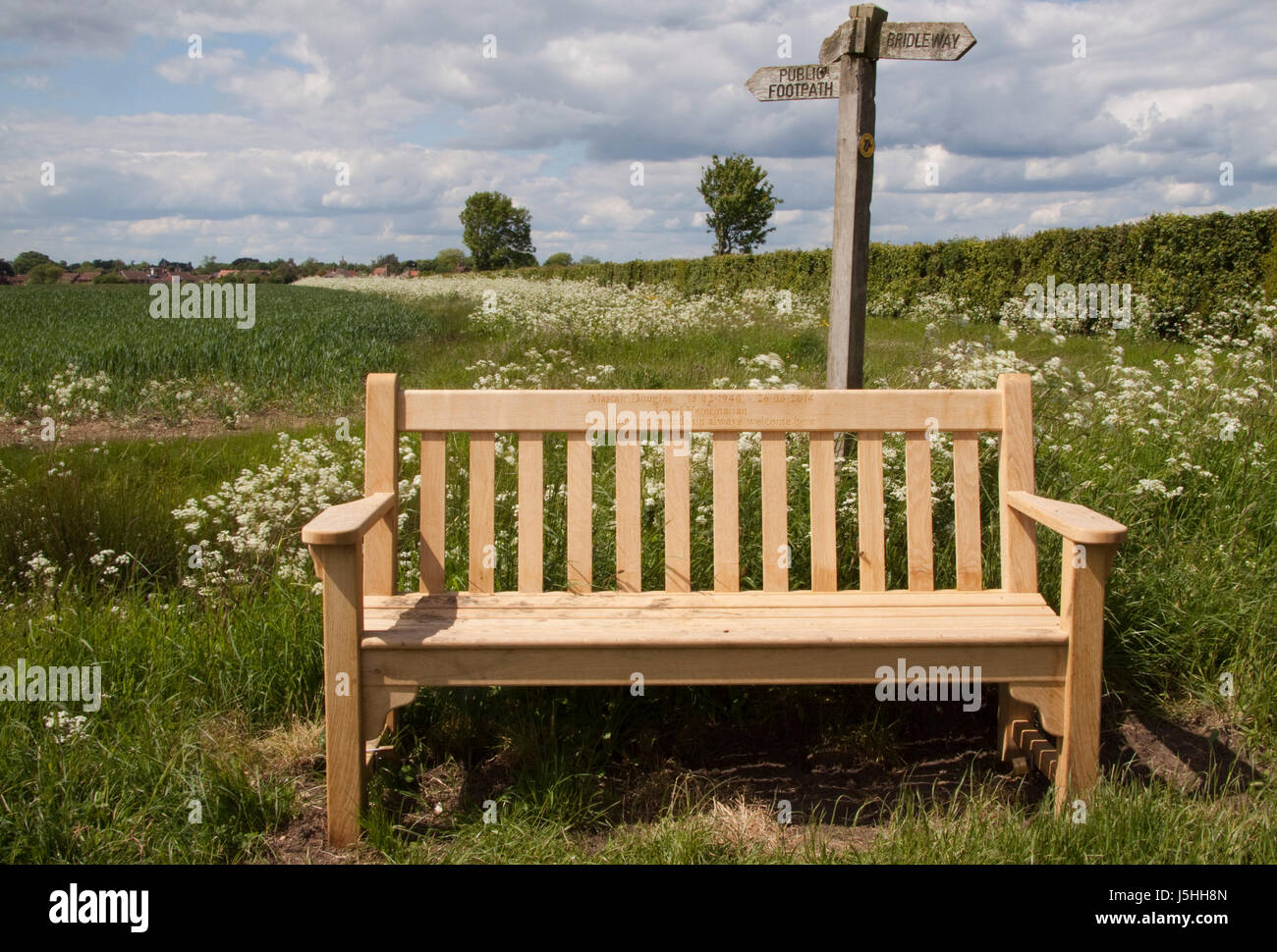 Memorial wooden bench by footpath signpost - Stock Image