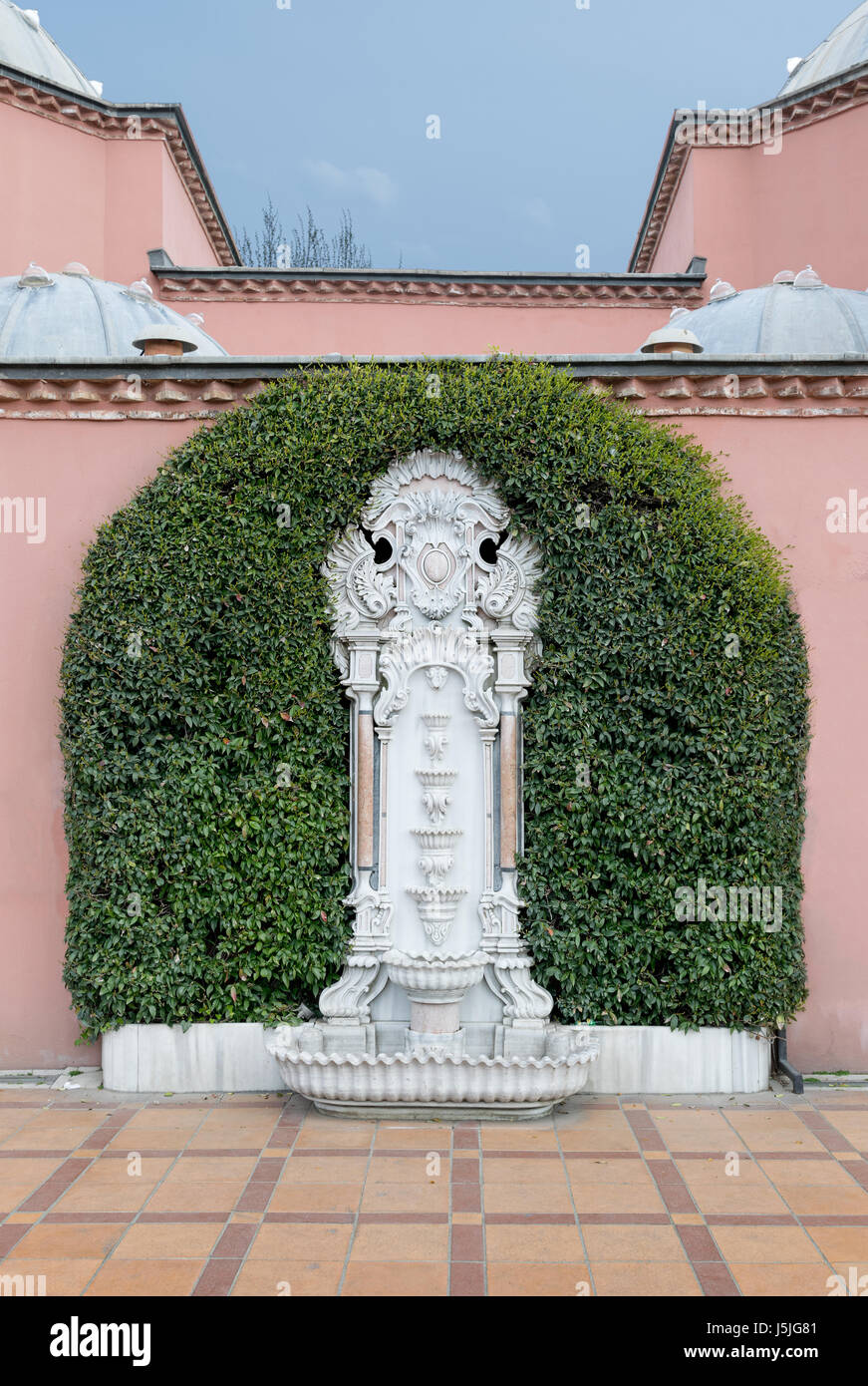 White marble sculpted wall fountain surrounded by green leaves over pink stone wall and tiled orange ceramic floor - Stock Image