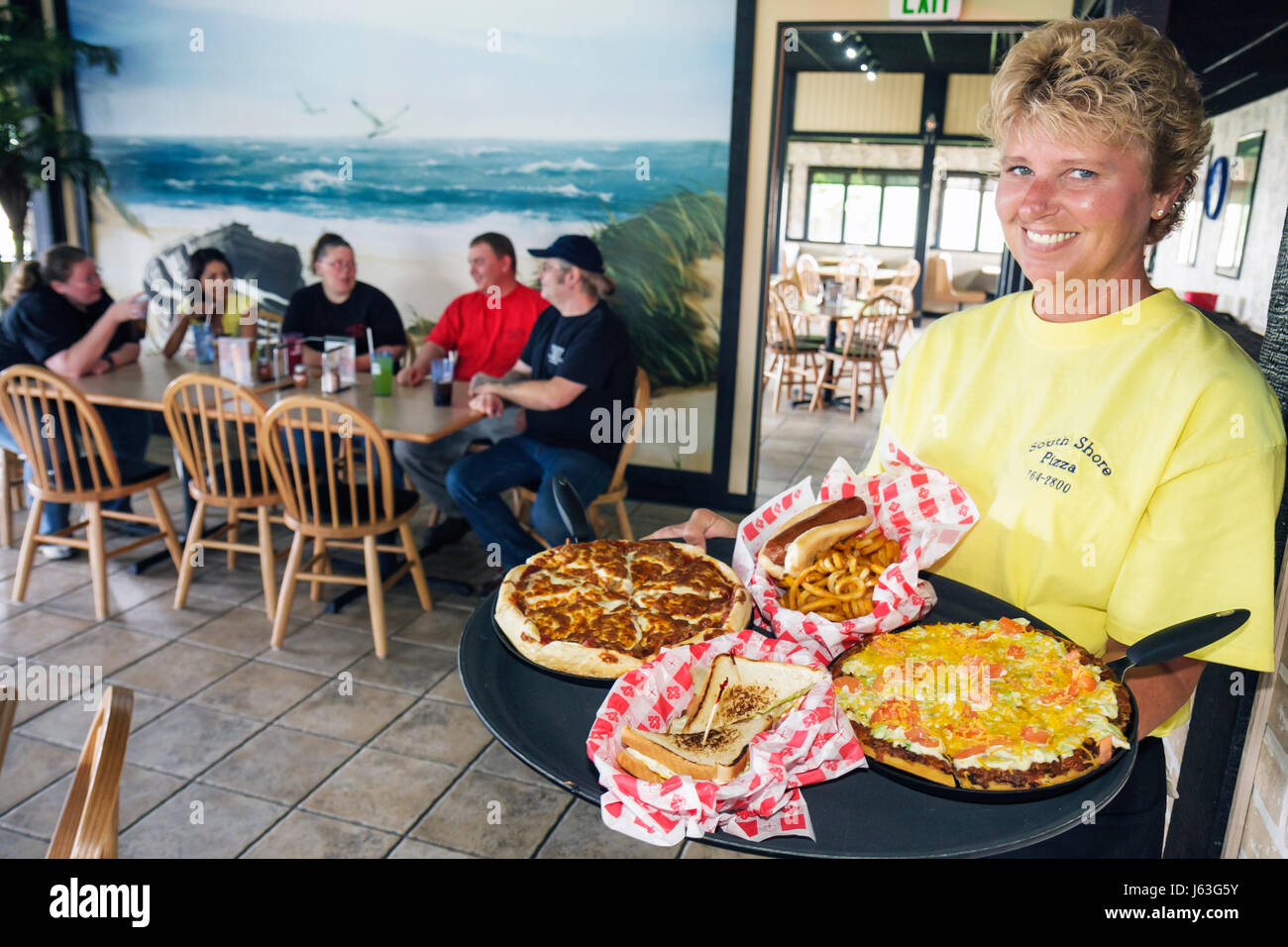 Indiana Portage South Shore Pizza restaurant business food woman waitress tray sandwich hot dog table meal lunch - Stock Image