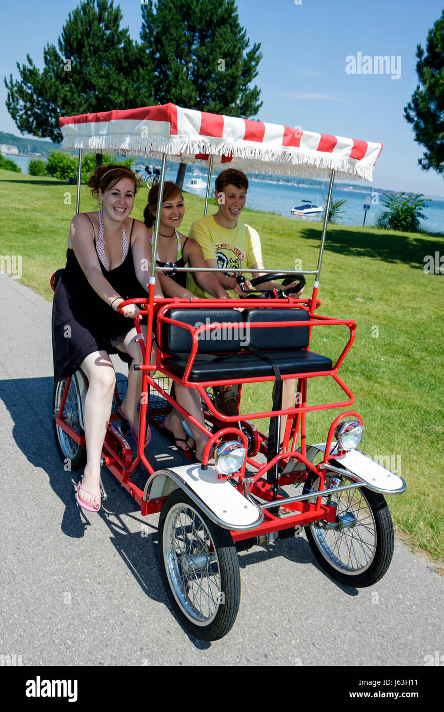 Michigan Traverse City West Arm Grand Traverse Bay Clinch Park boy two girls teen Surrey four wheel bicycle red - Stock Image