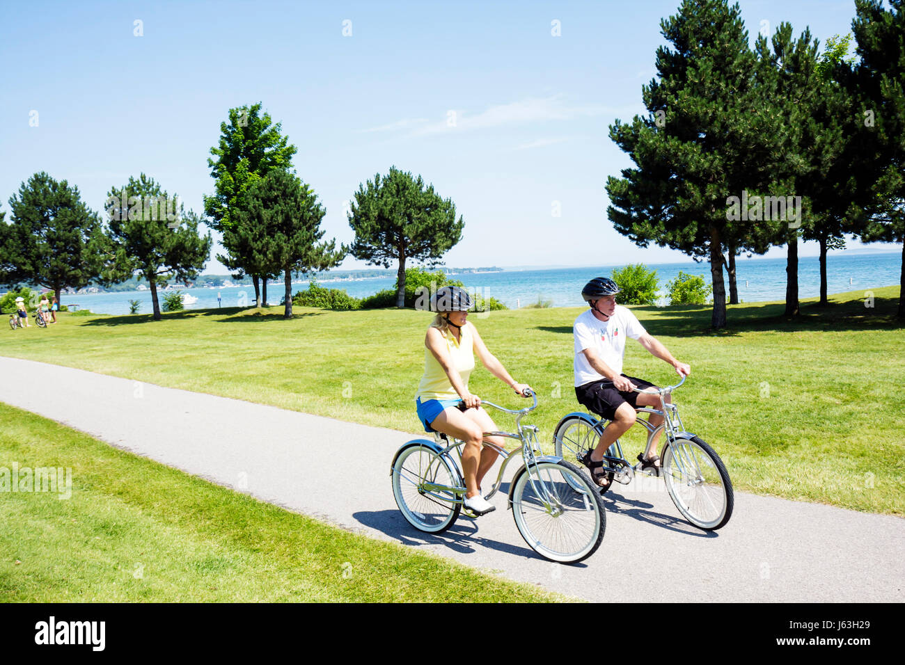 Michigan Traverse City West Arm Grand Traverse Bay Clinch Park woman man couple bicycle ride trail enjoy shore exercise - Stock Image