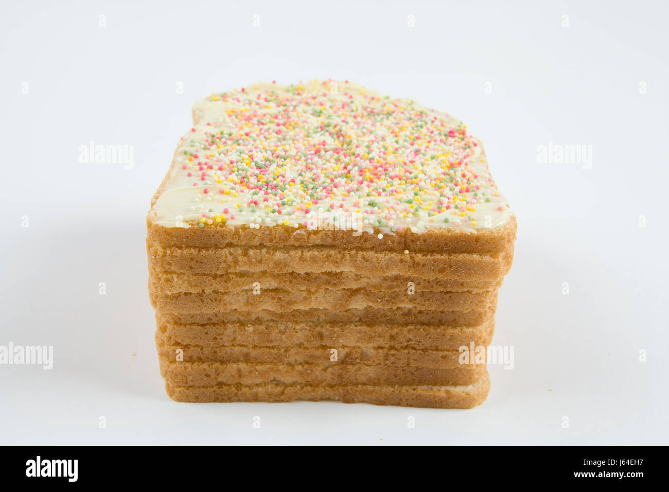 a quirky icing birthday bread covered with sprinkles on white background - Stock Image