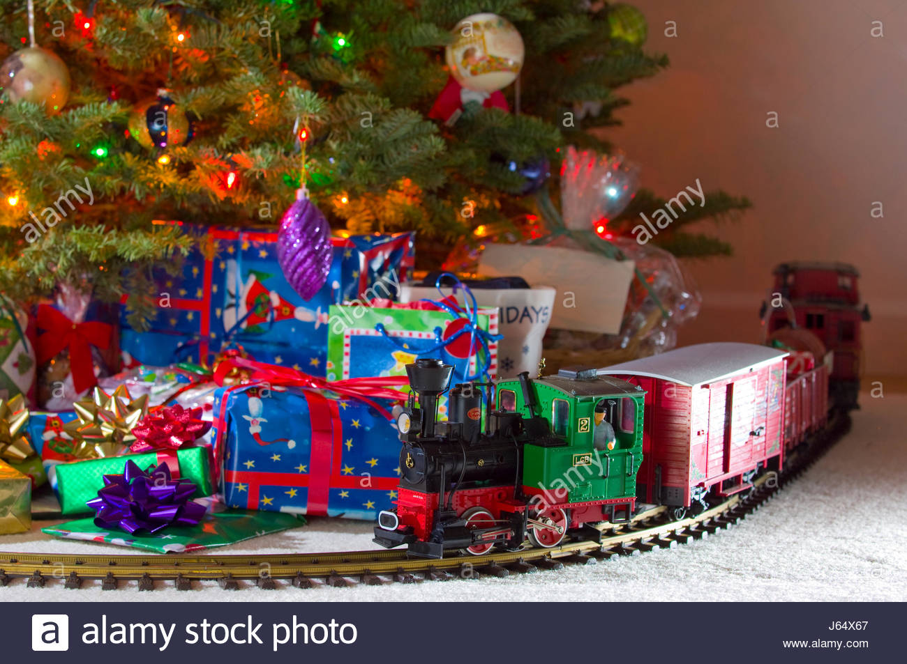 Toy electronic train on track in front of decorated Christmas tree with many wrapped presents piled beneath it. Stock Photo
