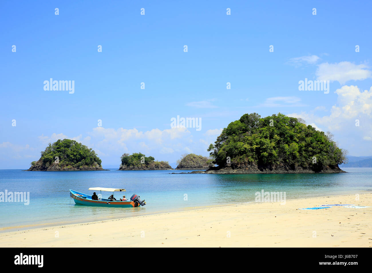 Beach with Small Isles and a Dive Boat. Coiba National Park, Panama - Stock Image