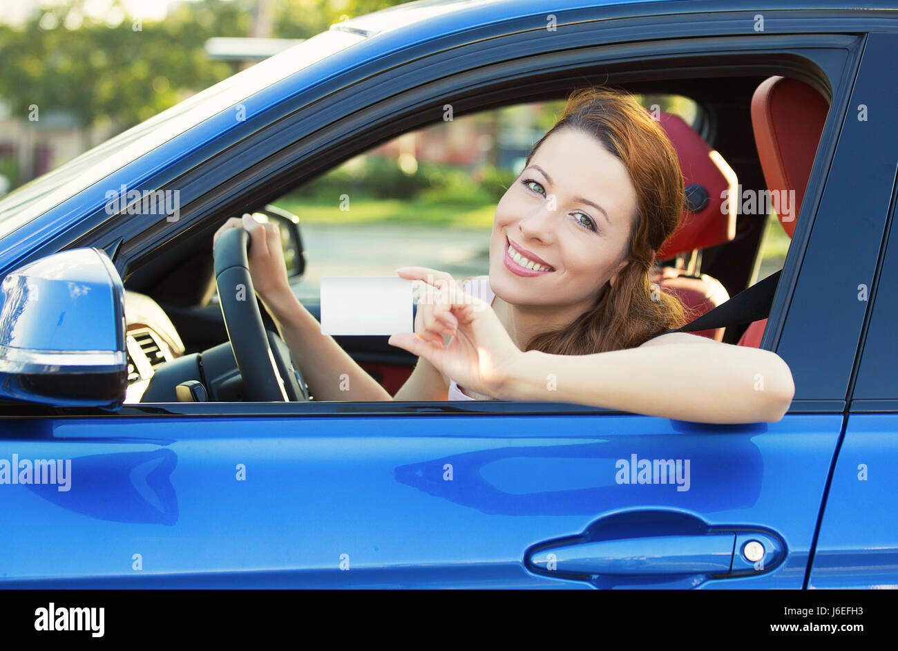 Young woman in new car showing blank drivers license or sign out, through side car window. Happy lovely female model - Stock Image